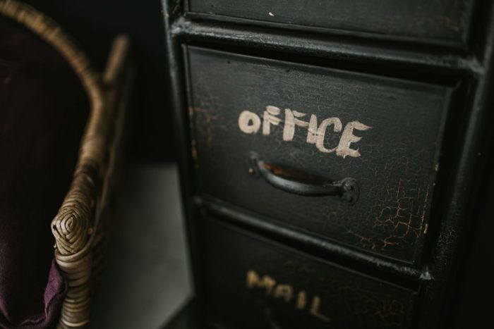 archiving files in an old black file cabinet